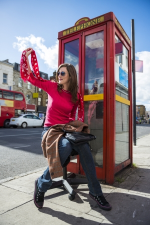 Low angle shot of fashionable young woman waving by street with red phone booth behind her photo