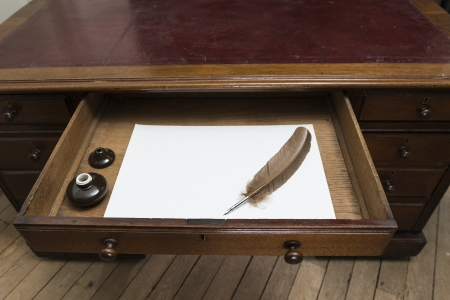 Vintage set with quill and ink pot on top of parchment paper inside writing desk drawer. photo
