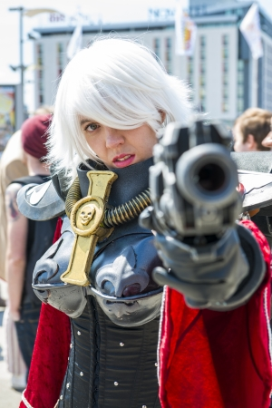 LONDON, UK - May 26: Warhammer Sister of Battle cosplayer pointing gun at camera outside the Excel Centre at the MCMExpo. May 26, 2013 in London.