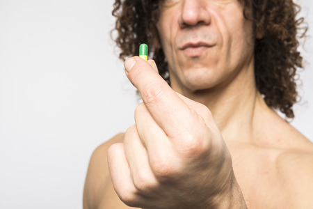 cropped shot: Cropped shot of bare chested mediterranean man holding colourful pill