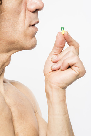 cropped shot: Cropped shot of bare chested mediterranean man taking colourful pill