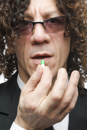 Cropped shot mediterranean man in a suit taking colourful pill photo