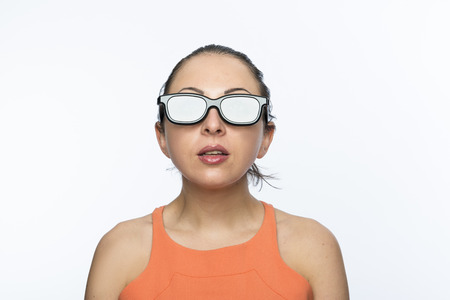 Portrait of beautiful caucasian woman wearing large 3D cinema glasses looking enthralled photo