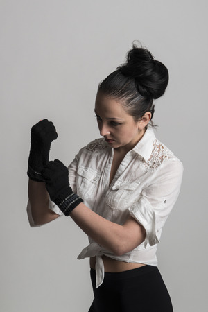 fingerless gloves: Fashion portrait of beautiful caucasian female model wearing white shirt and wearing fingerless gloves