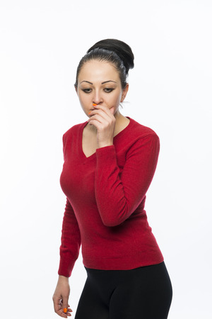 Portrait of beautiful caucasian woman wearing red dress and looking concerned covering her mouth photo