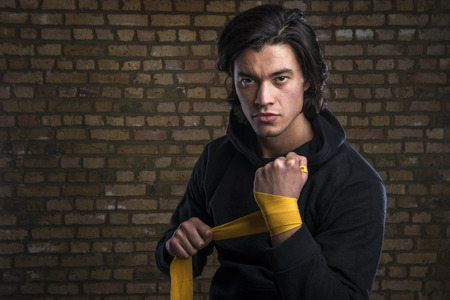 Young Malaysian boxer  wearing hoodie and wrapping straps around hands photo