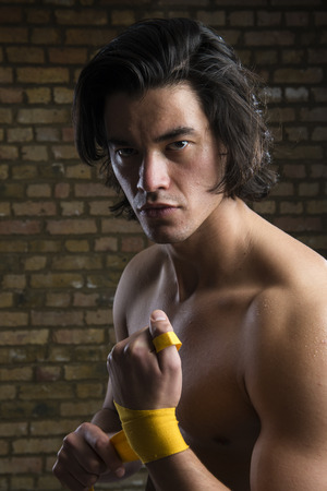 Bare chested young Malaysian boxer wrapping straps around hands photo