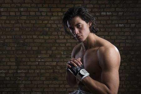 Bare chested young Malaysian boxer wearing fingerless boxing gloves photo
