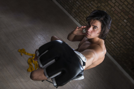fingerless gloves: High angle shot of bare chested young Malaysian boxer punching in the direction of the camera with fingerless gloves