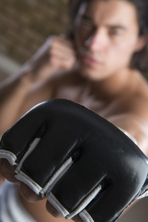 fingerless gloves: Bare chested boxer punching in the direction of the camera with fingerless gloves
