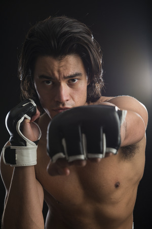 key punching: Bare chested young Malaysian boxer punching in the direction of the camera with fingerless gloves