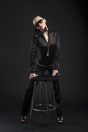 intimidating: Full length shot of intimidating Caucasian woman wearing black bodysuit and sunglasses, against black background Stock Photo