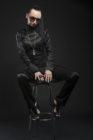 Full length shot of beautiful Caucasian woman wearing black bodysuit and sitting on a posing stool, against black background photo