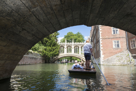 punter: CAMBRIDGE, UK - AUGUST 18: Professional punter passing under the oldest bridge in Cambridge, Claire bridge, in busy River Cam and the Bridge of Sights in the far horizon. August 18, 2013 in Cambridge. Editorial