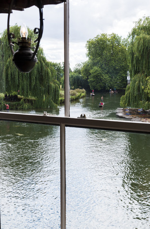 oillamp: CAMBRIDGE, UK - AUGUST 18: River Cam with tourist punters in gondolas and park full of trees in the background viewed through old window with oil-lamp styled light. August 18, 2013 in Cambridge.