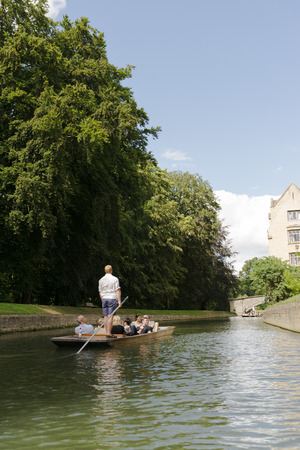 punter: CAMBRIDGE, UK - AUGUST 18: Professional punter in busy River Cam with tree lined bank to one side and bridge in the far horizon. August 18, 2013 in Cambridge.