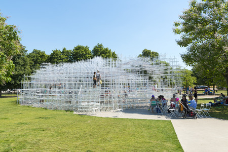 LONDON, UK - AUGUST 01: Park visitors enjoying the sunny weather at the Serpentine gallerys pavilion designed by architect Sou Fujimoto in Kensington Gardens. August 01, 2013 in London. Editorial