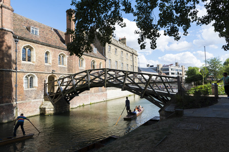 punter: CAMBRIDGE, UK - AUGUST 18: Tourist punter in gondola in River Cam passing under Mathematical bridge with park full of trees in the background. August 18, 2013 in Cambridge.