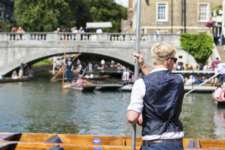 punter: CAMBRIDGE, UK - AUGUST 18: Professional punter in Silver Street with busy River Cam full of tourists in gondolas in background. August 18, 2013 in Cambridge.