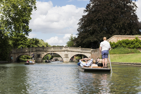punter: CAMBRIDGE, UK - AUGUST 18: Professional punter in busy River Cam with tree lined bank to one side and the oldest bridge in Cambridge, Claire bridge, in the far horizon. August 18, 2013 in Cambridge.