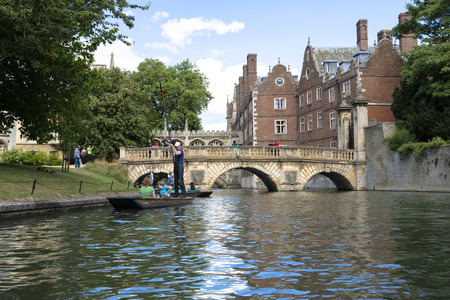 punter: CAMBRIDGE, UK - AUGUST 18: Turist punter in River Cam with tree lined bank to one side and the olderst bridge in Cambridge, Claire bridge, followed by the Bridge of Sights in the far horizon. August 18, 2013 in Cambridge.