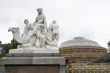LONDON, UK - SEPTEMBER 14: Detail of one of the four main statues in each corner of the Albert Memorial in Kensington Gardens, with Royal Albert Hall in the background. September 14, 2013 in London.
