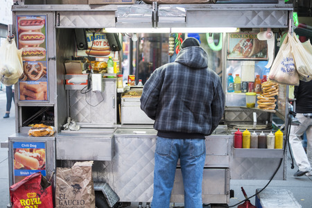 NEW YORK, US - NOVEMBER 24: Street corner food stand with seller from behind. November 24, 2013 in New York.