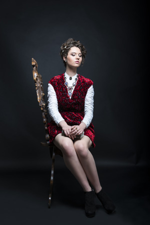 Portrait of beautiful Caucasian model in red Victorian-style velvet dress, seated on wooden chair photo