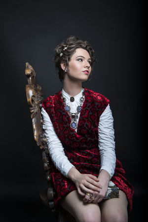 velvet dress: Portrait of beautiful Caucasian model in red Victorian-style velvet dress, seated on wooden chair