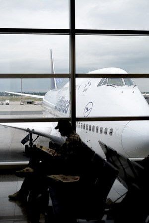 FRANKFURT, GERMANY - JULY 21: Silhouette of passenger waiting for flight in terminal with Lufthansa jumbo jet in perspective in the background.. July 21, 2014 in Frankfurt.