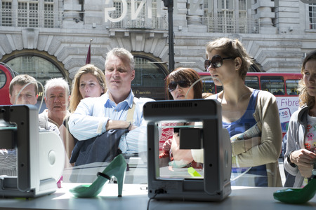 LONDON, UK - MAY 31: Pedestrians intrigued with 3D printer in United Nude shop window. The shop, based in Regent Street, has a line of products created on site by 3D printers. May 31, 2014 in London.