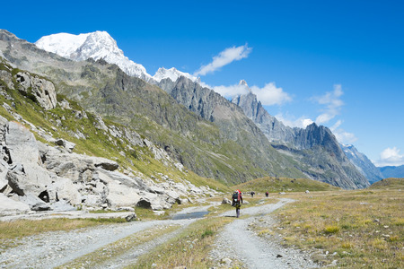 veny: VAL VENY, ITALY - AUGUST 27: Hikers on valley path with Limestone Pyramids in the background. The region is a stage of the popular Mont Blanc tour. August 27, 2014 in Val Veny.