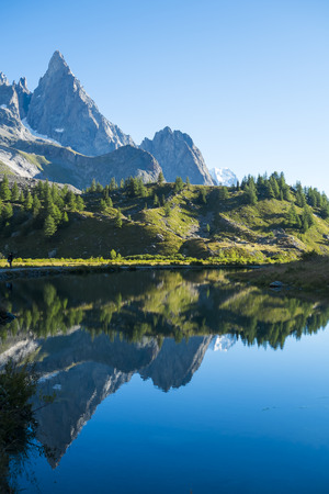 veny: Combal Needles reflected on Combal Lake water on a sunny day in Val Veny, in Italy. Stock Photo