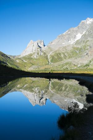 veny: Limestone Pyramids reflected on Combal Lake waters in Val Veny, Italy