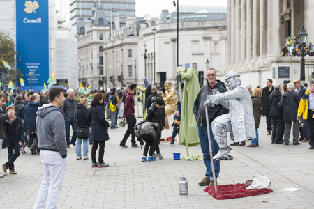 levitating: LONDON, UK - OCTOBER 26: Street artists levitating in busy Trafalgar Square. In central London, street artists must obtain a permit in order to perform in public spaces. October 26, 2014 in London. Editorial