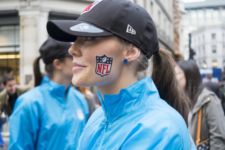 LONDON UK - SEPTEMBER 27: Profile portrait of beautiful girl with NFL logo painted on cheek. September 27 2014 in London. The street was closed to traffic to host NFL related games and events. Editorial