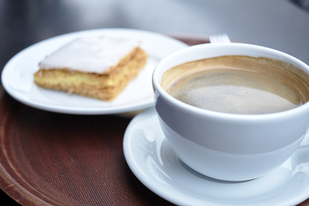 mille: Shallow depth of field shot of coffee cup with mille feuille in the blurred background Stock Photo