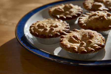 Plate of mince pies shot against the light on a wooden table photo