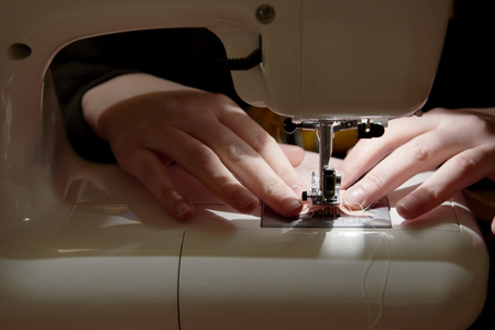 stitching machine: Detail of hands working on piece of fabric on automatic sewing machine
