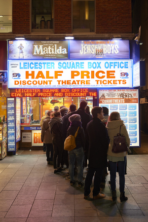 discounted: LONDON, UK - JANUARY 02: People lined up for discounted theatre tickets at night in Leicester Square. January 02, 2015 in London.