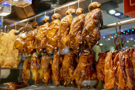 Detail of Chinese restaurant with traditional crispy ducks hanging on foggy display window in Londons Chinatown at night.