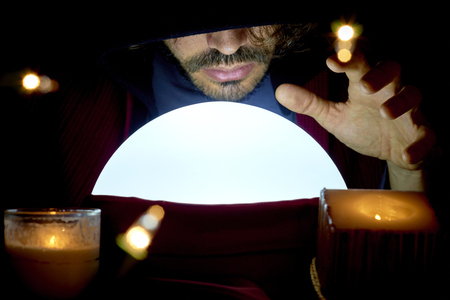 mage: Very low key portrait of hooded man with eyes covered reading fortune on bright crystall ball, surrounded by candle light.