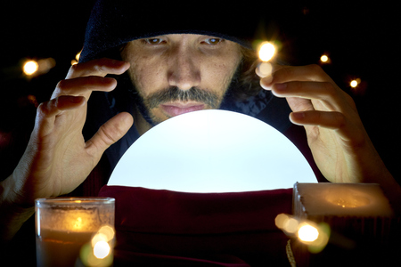 Very low key portrait of hooded man reading fortune on bright crystall ball, surrounded by candle light.