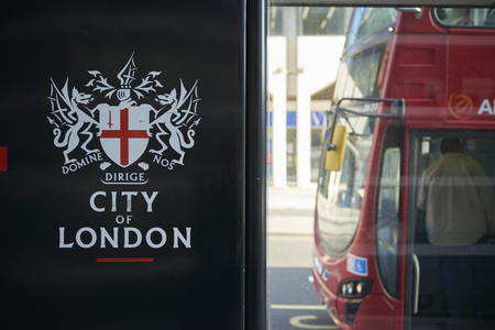 city coat of arms: LONDON, UK - APRIL 06: Detail of black City of London banner in bus stop featuring its coat of arms, with front of red bus in the background. April 06, 2015 in London. Editorial
