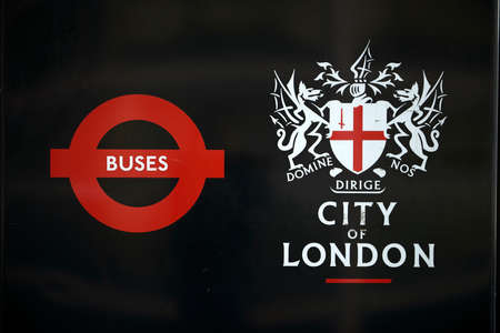 city coat of arms: LONDON, UK - APRIL 06: Detail of black City of London banner in bus stop featuring its coat of arms next to the Transport for London red logo. April 06, 2015 in London.