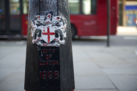 city coat of arms: LONDON, UK - APRIL 06: Detail of black City of London bollard featuring its coat of arms, with read of red bus in the blurred background. April 06, 2015 in London.