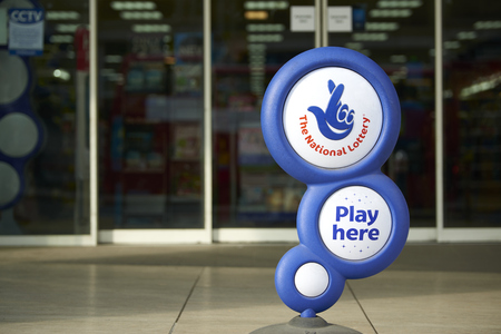 LONDON, UK - APRIL 07: Blue National lottery sign in front of shop, showing its crossed fingers logo. On 07 April 2015.