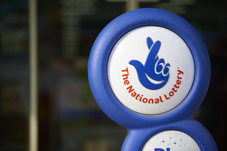 crossed fingers: LONDON, UK - APRIL 07: Close up of blue National lottery sign, showing its crossed fingers logo. On 07 April 2015. Editorial