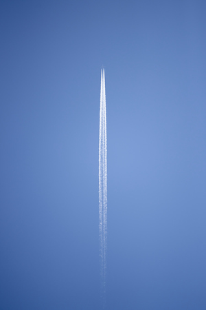 condensation: Aircraft flying high above leaving well-defined condensation trail behind it.