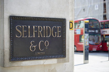 oxford street: LONDON, UK - APRIL 22: Shop sign at the corner of famous department store Selfridge & Co., in Oxford Street, with red double-decker bus in the background. April 22, 2015 in London.